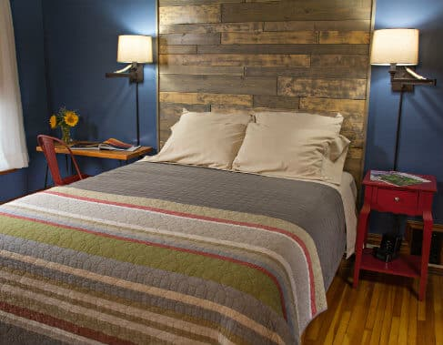 Blue guest room with wood floors, bed with striped quilt and shiplap headboard, two nightstands and reading lights