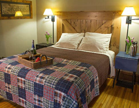 Guest room with wood floors, bed with rustic wood headboard, nightstands and reading lights, tray of strawberries and champagne,
