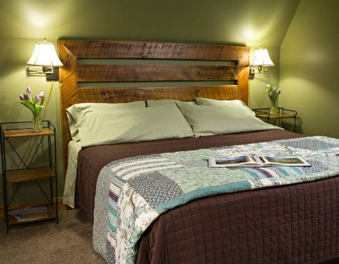 Green guest room with sloped ceilings, wood slatted bed with flanking nightstands and reading lights