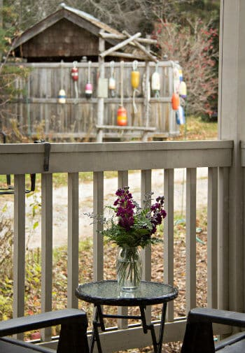 Porch view of round table topped with fresh flowers, wood railing, and trees in the background