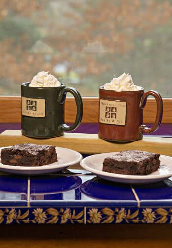 Red and green mugs filled with hot cocoa and whipped cream and two plates topped with brownies