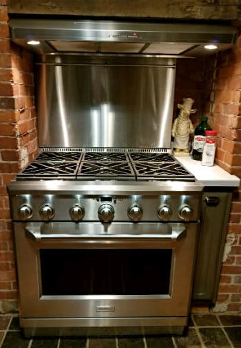 Stainless steel range with six gas burners surrounded by red brick walls