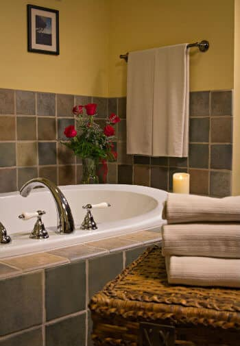 White soaking tub surrounded by tile and topped with fresh red roses