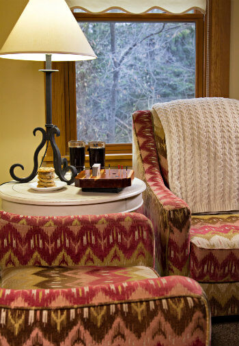 Colorful southwestern styled upholstered chairs flanking a white round table with lamp, cookies, and drinks