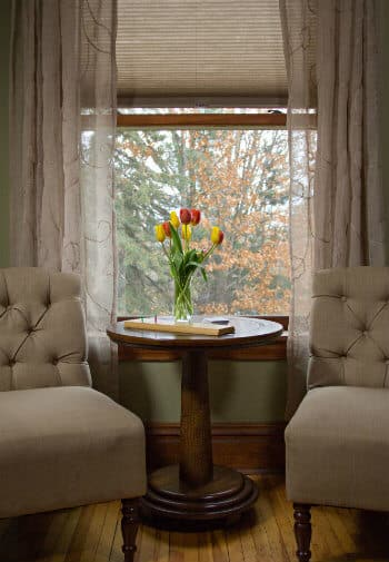 Sitting area with two upholstered chairs flanking round wood table in front of window