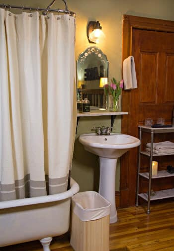 Green bathroom with wood floors, white clawfoot tub and pedestal sink, white towels and fresh flowers