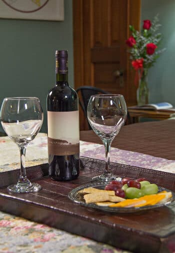 Wood tray topped with two wine glasses, bottle of wine, grapes, cheese and crackers with red roses in the background