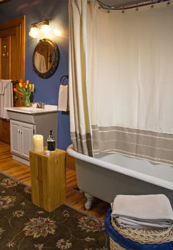 Blue bathroom with white clawfoot tub, wood floors, area rug, white towels and fresh flowers