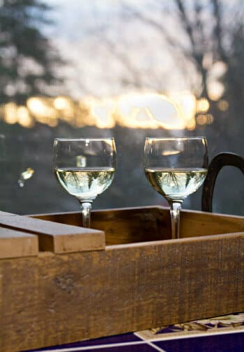 Rustic wood tray topped with two glasses of white wine outside amidst the setting sun