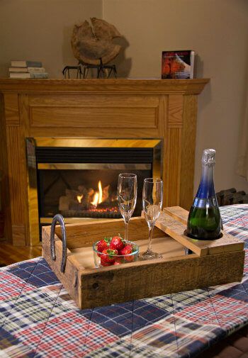 Rustic wood tray topped with fresh red strawberries and champagne on corner of bed and a warm glowing fireplace in the background