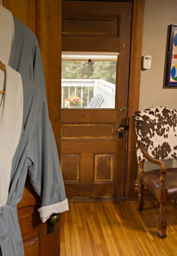 Guest room door with window, wood floors, sitting chair, and two robes hanging in the foreground