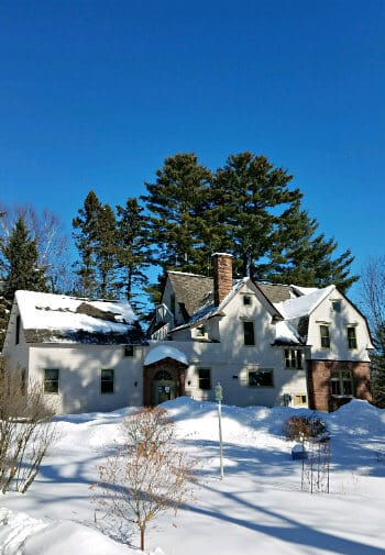 Outdoor front scape of the inn with snow covering the ground and roof with tall pine trees behind against clear blue sky.