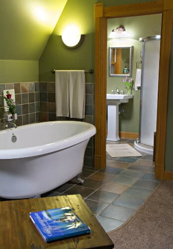 Green bathroom with white claw foot tub, colorful tile floors and wall, pedestal sink and shower in the background