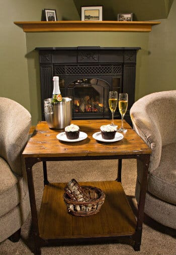 Two upholstered club chairs with a wood table in between topped with champagne and dessert and fireplace in the background