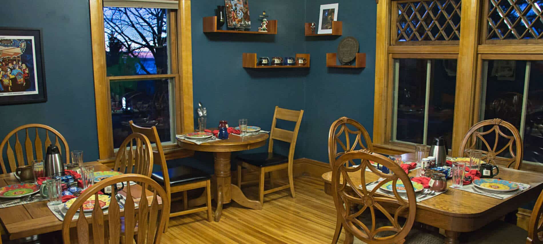 Blue dining room with wood floors, three individual dining tables set for breakfast, and large windows