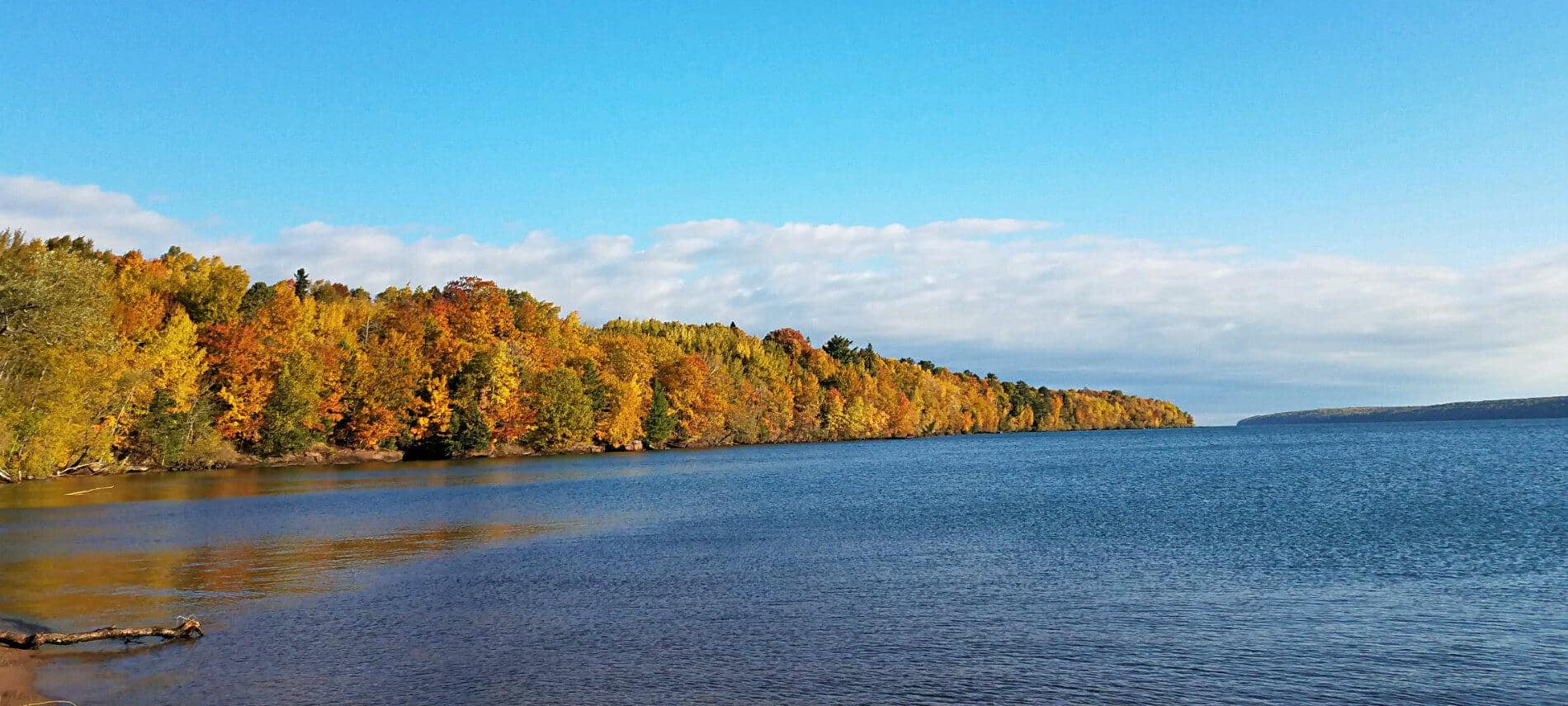 Blue water of Lake Superior bordered by fall colored trees and blue sky