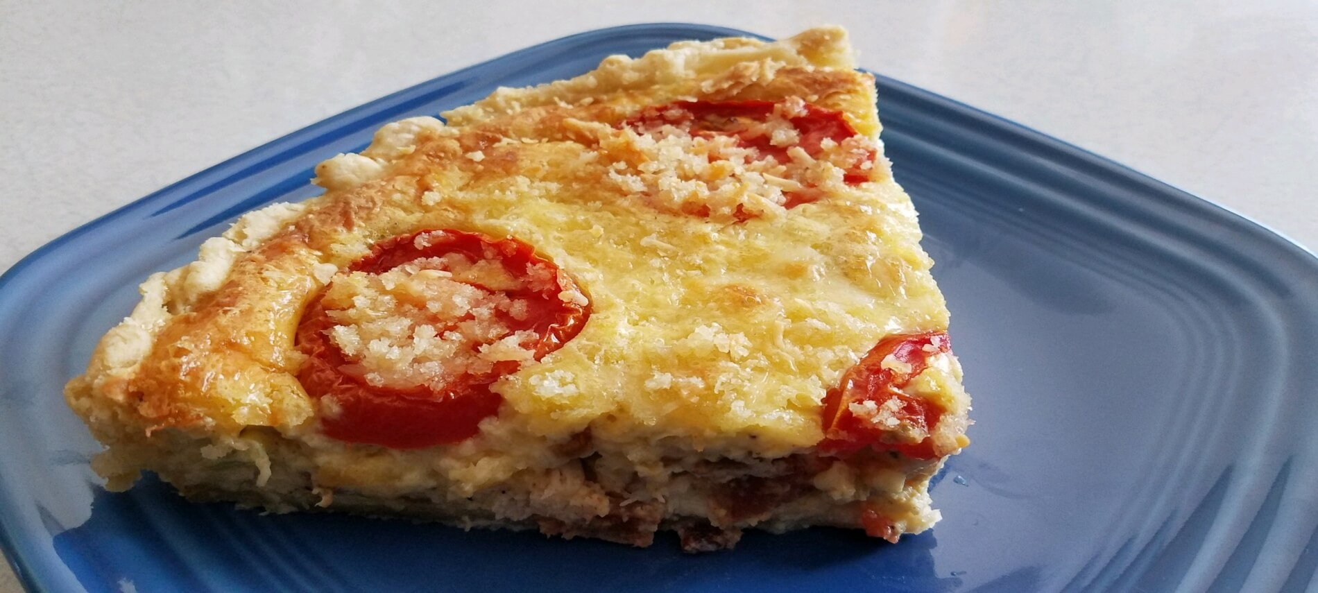 Slice of golden quiche topped with tomatoes on a blue plate