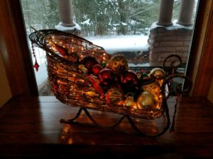 wicker tabletop sleigh with white lights filled with red and gold Christmas ornaments on wood table in front of large window